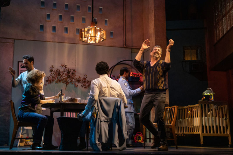 An older man dances around a dinner table filled with his family and guests in a scene from THE BAND'S VISIT.